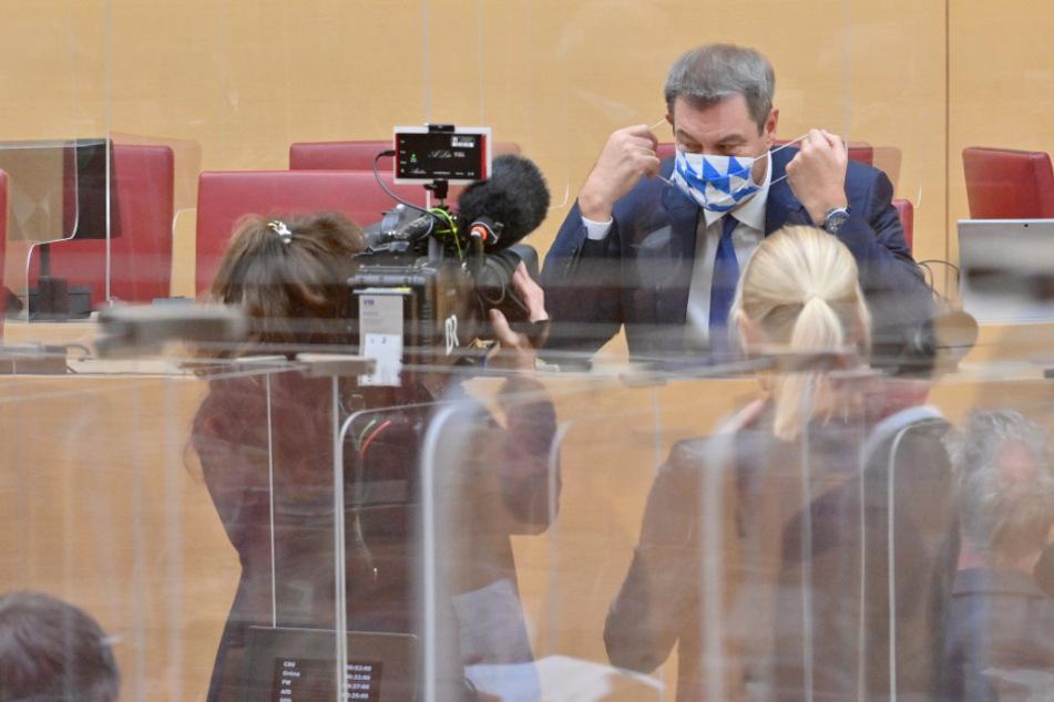 Markus Söder (CSU), Ministerpräsident von Bayern, setzt sich vor Beginn der Sitzung des bayerischen Landtags hinter einer Plexiglasabtrennung seinen Mund-Nasen-Schutz auf.