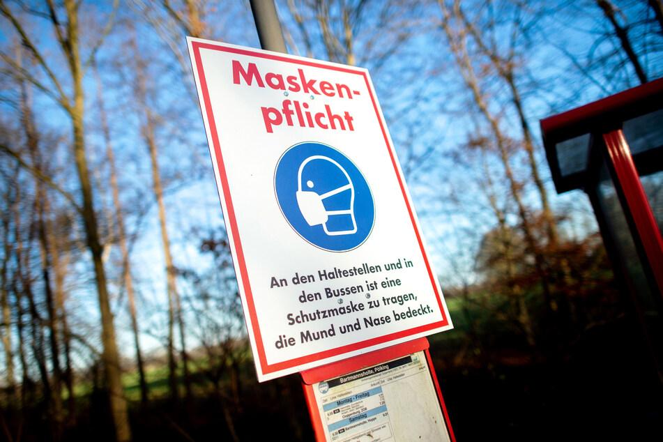 """Ein Schild mit der Aufschrift """"Maskenpflicht"""" hängt an einer Bushaltestelle nahe der Ortschaft Bartmannsholte. Die Corona-Infektionen in Deutschland sind auch am Sonntag weiterhin auf einem hohen NIveau."""