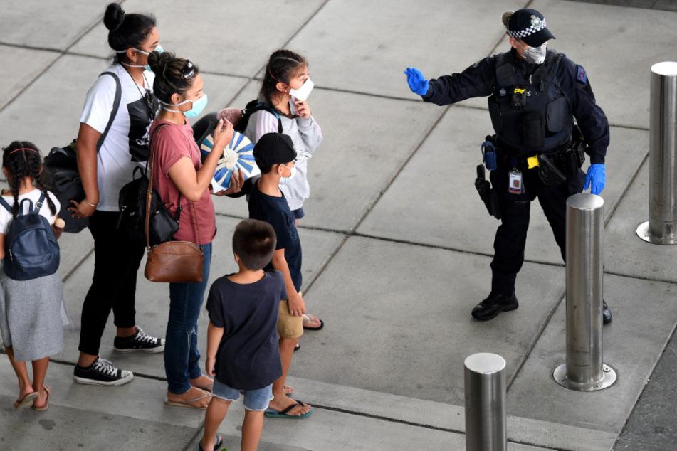 Eine Polizistin mit Mundschutz leitet Passagiere, die mit einem vom US-Außenministerium gecharterten Flugzeug ins Land zurückgeholt wurden.
