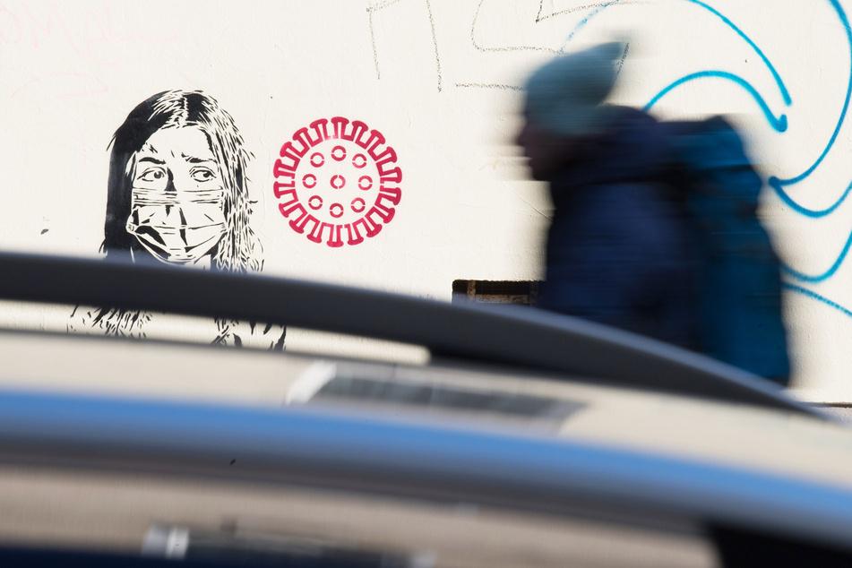 Ein Graffiti mit der Darstellung eines Coronavirus ist an einer Hauswand im Berliner Winsviertel zu sehen.