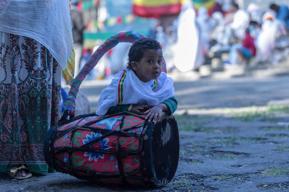 Äthiopien, Addis Abeba: Ein Kind spielt während eines Gottesdienstes zur äthiopischen Weihnacht in der Bale-Wold-Kirche mit einer Trommel, die vom Chor benutzt wird.