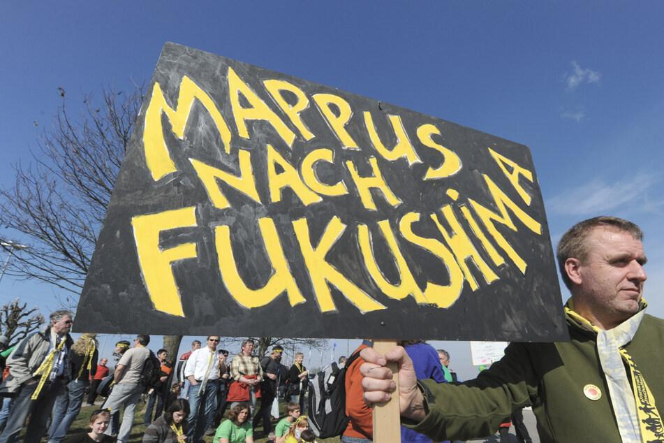 """Ein Demonstrant hält 2011 vor dem Atomkraftwerk Neckarwestheim (Kreis Heilbronn) ein Schild mit der Aufschrift """"Mappus nach Fukushima"""" in der Hand. (Archiv)"""