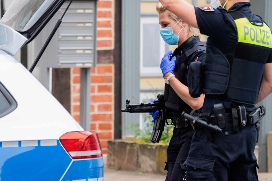 Schwer bewaffnete Polizisten stehen in der Nähe vom Amtsgericht Celle vor dem Kofferraum ihres Autos.