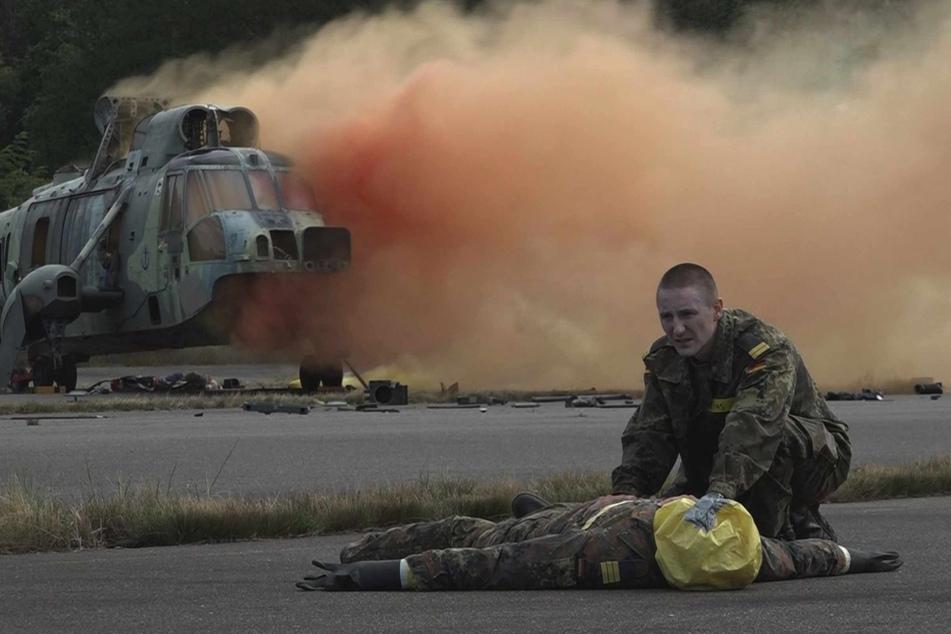 Ein Sanitäter kümmert sich um eine verletzte Person. Im Hintergrund steht der Hubschrauber in Flammen. Zum Glück nur eine Übung.