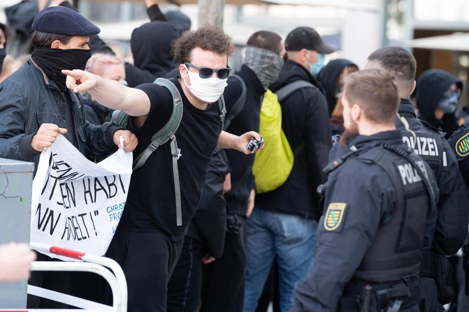 Ein Gegendemonstrant diskutiert während der Pegida-Kundgebung mit einem Polizisten.