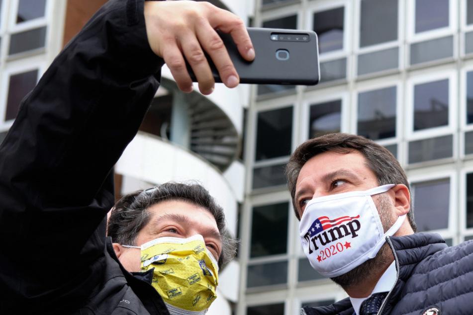 Matteo Salvini (47, rechts), der Chef der rechten italienischen Lega, lässt sich, mit einer Maske die für den US-Präsidenten Trump wirbt, fotografieren bei einem Protest gegen die Steuergesetze vor dem Sitz der Finanzbehörde.