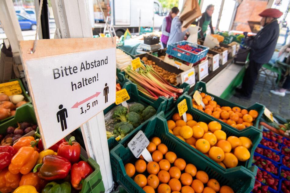 """Ein Schild """"Bitte Abstand halten"""" hängt bei einem Obst- und Gemüsehändler auf einem Wochenmarkt."""