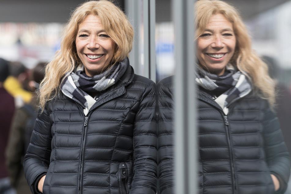"""Die Initiatorin des Modellprojekts """"Öffnen mit Sicherheit"""", Notärztin Lisa Federle, steht in der Tübinger Innenstadt vor einer Corona-Schnelltest-Station und spiegelt sich in einer Scheibe."""