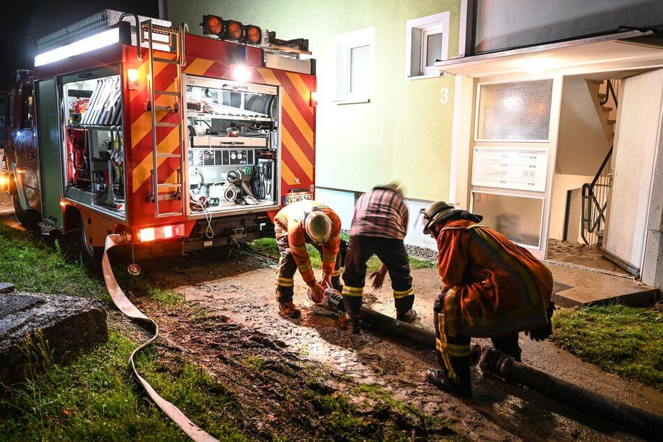 Feuerwehrmänner bereiten einen Schlauch vor, um einen Keller in Wuppertal auszupumpen, der beim Hochwasser vollgelaufen ist. In der Nacht war wegen des Starkregens das Wohngebiet Epplingser Halde überschwemmt worden.