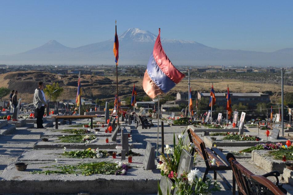Armenien, Yerevan: Angehörige stehen am Jahrestag des Kriegsbeginns um die umkämpfte Region Berg-Karabach auf einem Soldatenfriedhof.