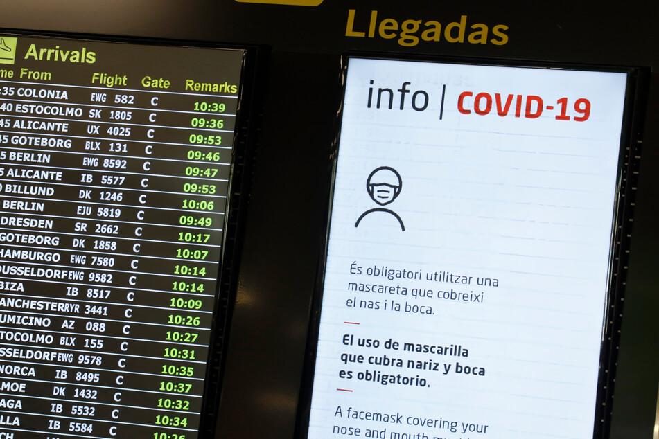 Anzeigetafeln zeigen die ankommenden Flüge am Flughafen von Palma de Mallorca und Hinweise zum Tragen von Mund-Nasen-Schutz im Gebäude an.