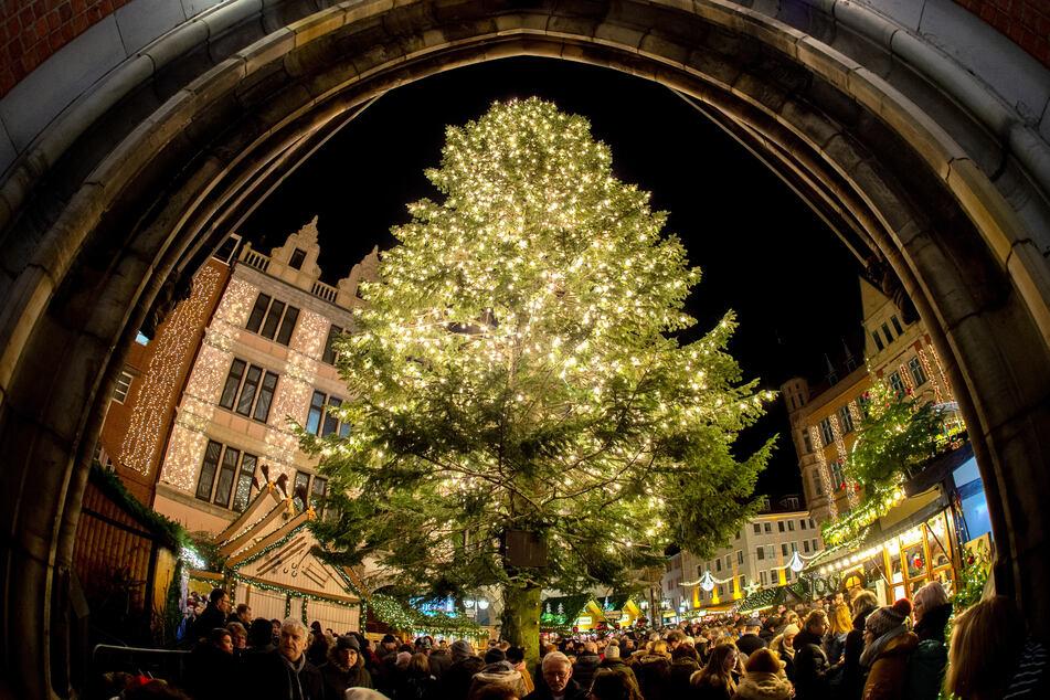 Besucher gehen vor dem Eingangsbogen der Marktkirche in der historischen Innenstadt von Hannover an einem mit Lichtern geschmückten Tannenbaum auf dem Weihnachtsmarkt vorbei.