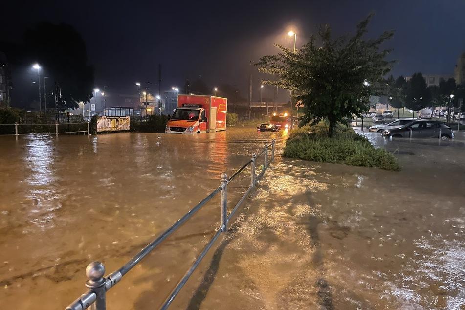 Ein Rettungswagen und Autos stehen in Hagen auf einer überfluteten Straße.