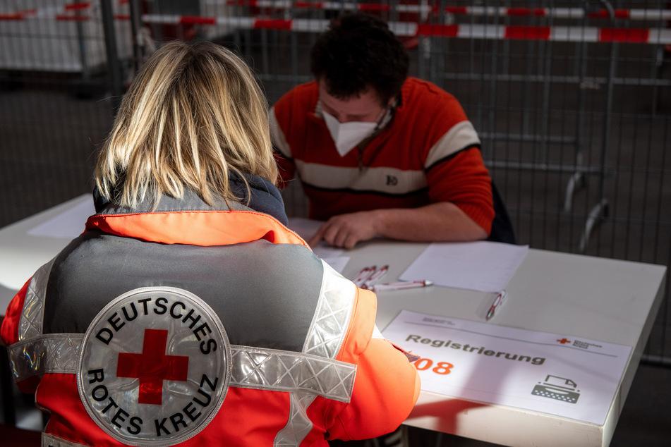 Eine Mitarbeiterin des Deutschen Roten Kreuzes simuliert die Registrierung im Messezentrum. (Symbolbild)