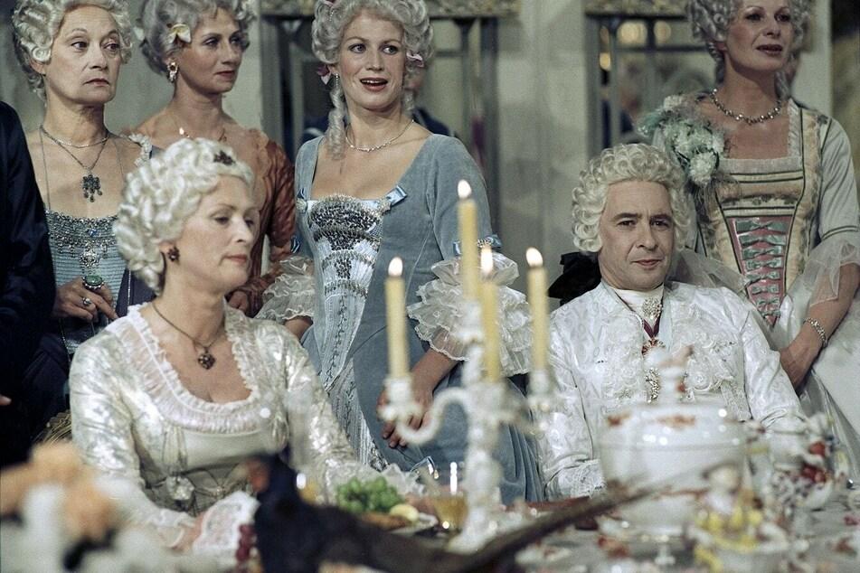 Mit dem Tode August des Starken 1733 beginnt auf mehreren Ebenen der Kampf um seine Nachfolge. Sachsens Schicksal wird zunehmend von einem jungen Adligen gelenkt, der sich vom Pagen August des Starken bis zum Premierminister hochgearbeitet hat, dem Grafen Heinrich von Brühl (Ezard Haußmann, sitzend, 1. Reihe, r.).