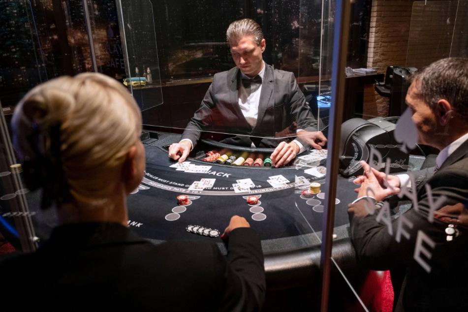 Ein Croupier (M) gibt in der Spielbank Stuttgart während eines Pressetermins an einem Black Jack Tisch Karten aus.