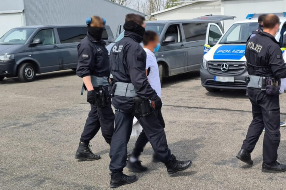 Polizisten führen einige Tatverdächtige ab.