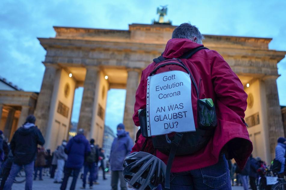 """Ein Transparent mit der Aufschrift """"Gott, Evolution, Corona, an was glaubst du?"""" trägt ein Teilnehmer einer Querdenker-Kundgebung im Januar 2021 vor dem Brandenburger Tor auf dem Rücken."""