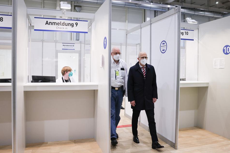 Peter Tschentscher (SPD, r) und Dirk Heinrich, ärztlicher Leiter des Impfzentrum Hamburg, gehen durch das Impfzentrum in den Messehallen.