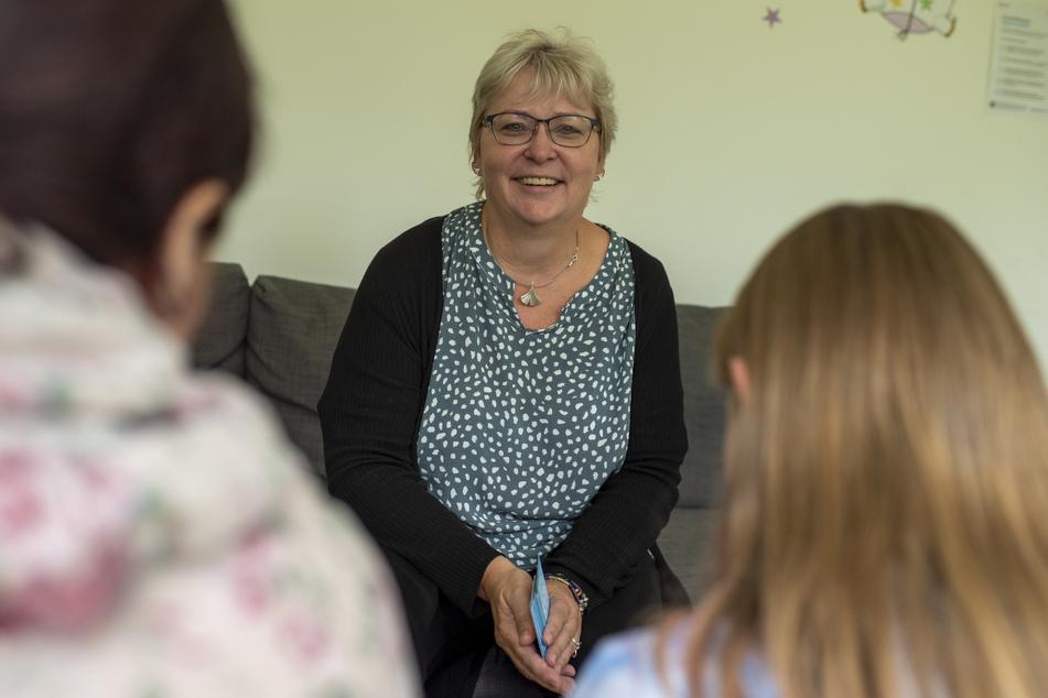 Anja Groß (50), Geschäftsführerin ambulante Dienste, spricht mit einer Frau und einem Mädchen aus einer Wohngruppe.