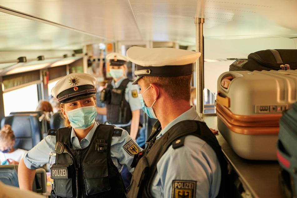 Beamte der Bundespolizei und Mitarbeiter der DB Sicherheit gehen durch einem IC kurz vor dem Berliner Hauptbahnhof und kontrollieren, ob die coronabedingte Maskenpflicht eingehalten wird.