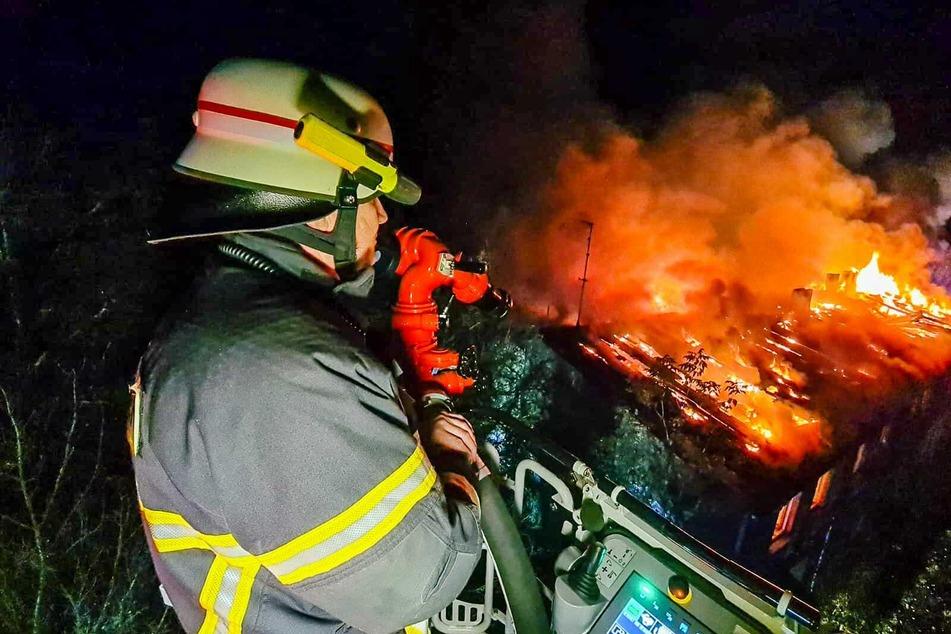 Ein Feuerwehrmann steht auf einer Drehleiter und verschafft sich von oben einen Überblick über das Brandgeschehen.
