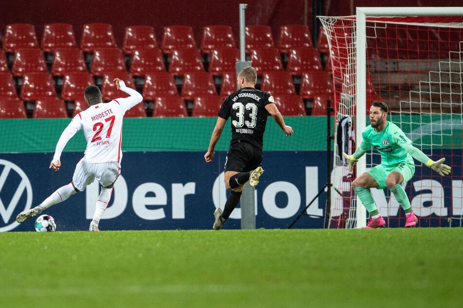 Kölns Anthony Modeste (l.) trifft gegen Osnabrücks Torhüter Philipp Kühn (r.) zur 1:0-Führung.