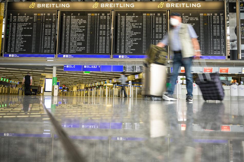 Nur wenige Reisende gehen mit Gepäck durch die Abflughalle im Terminal 1 am Flughafen Frankfurt.
