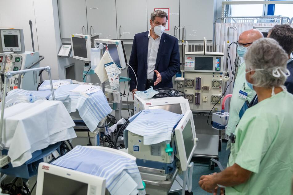 Markus Söder (l, CSU), bayerischer Ministerpräsident, unterhält sich bei einem Besuch im Klinikum Nürnberg Süd vor der Intensivüberwachungspflege mit Ärzten, in einem Raum in dem Beatmungsgeräte (im Vordergrund) zum Einsatz bereit stehen.