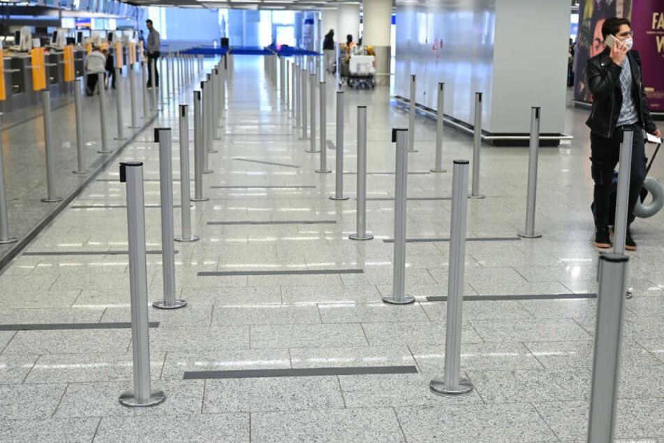 Bodenmarkierungen sind im Wartebereich vor den Check-In-Schaltern auf dem Boden am Frankfurter Flughafen angebracht.