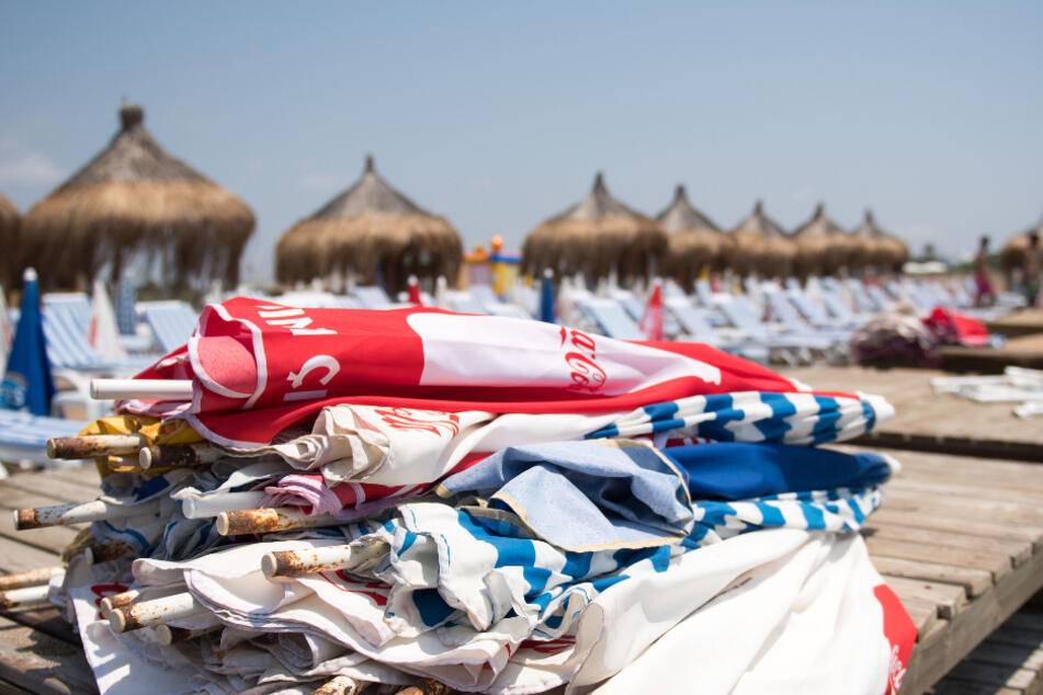 Sonnenschirme liegen am Strand von Lara auf leeren Strandliegen.