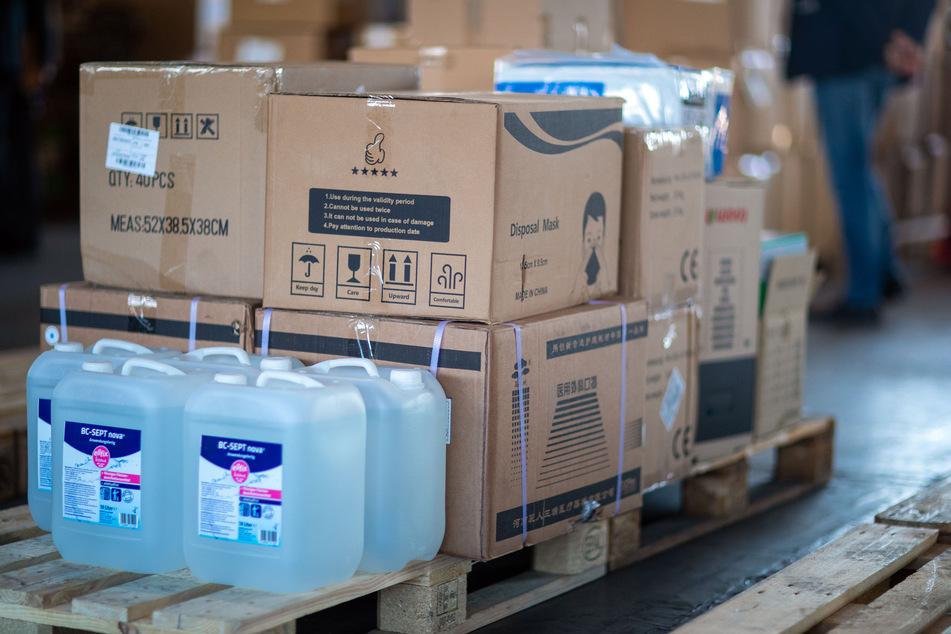 Paletten voller Kartons mit Schutzmasken und Kanister mit Desinfektionsmittel stehen in einem Lager.