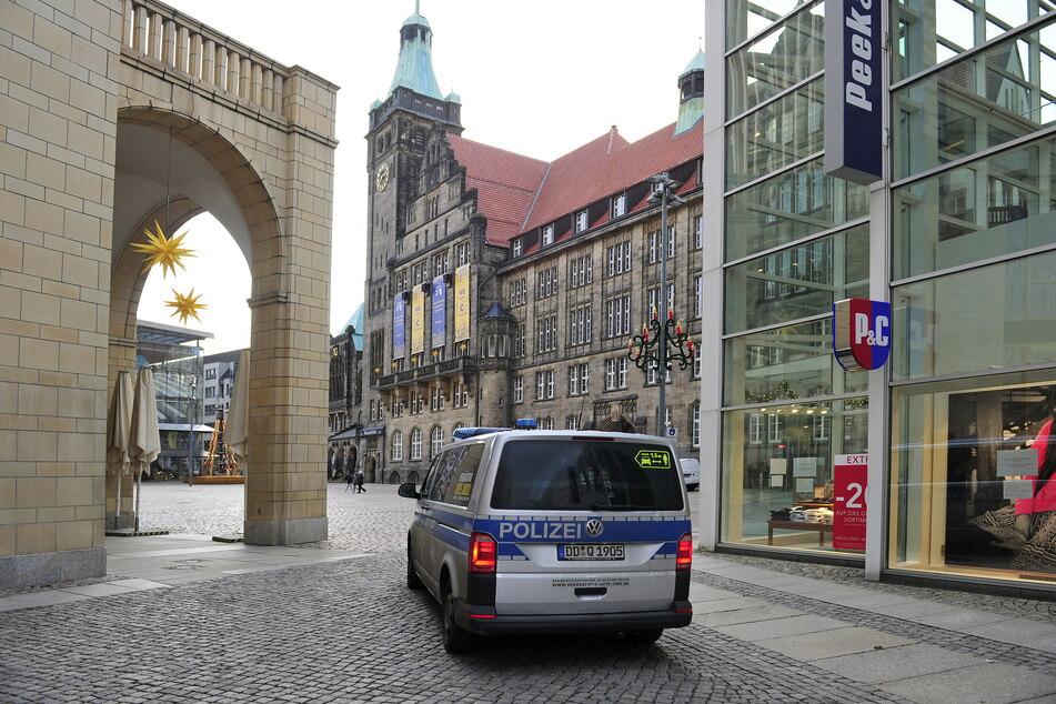 Ein Polizeiwagen fährt auf dem Neumarkt vor dem Rathaus Streife.