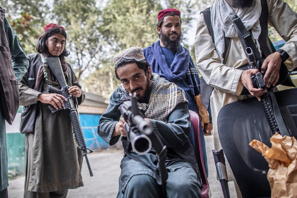 Ein junger Taliban-Kämpfer zielt zum Spaß mit seinem Gewehr in Richtung Fotograf.