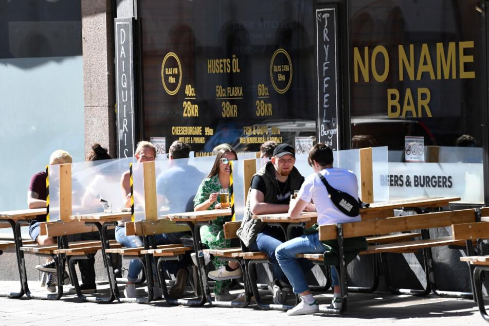 Schweden, Stockholm: Trennwände wurden zwischen den Tischen eines Restaurants zum Schutz der Kunden angebracht.