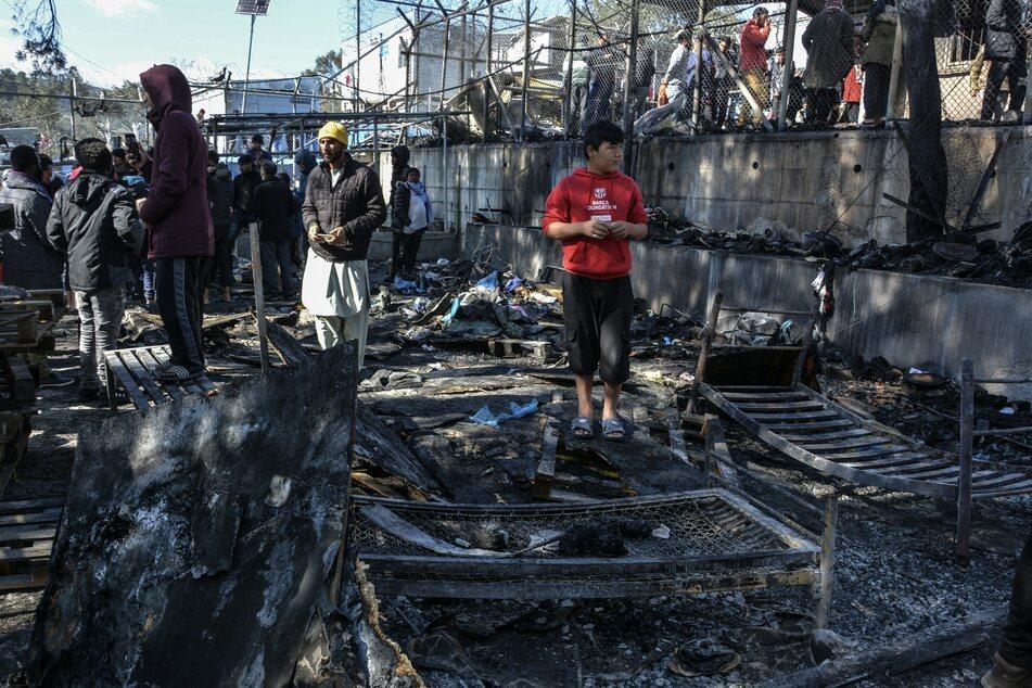 Moria: Migranten stehen auf den abgebrannten Überresten eines Containerhauses. (Archivbild)