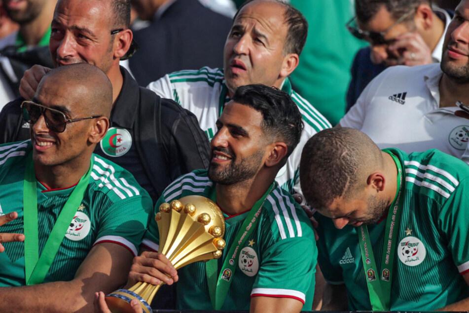 Algerien, Algier: Riyad Mahrez hält die Trophäe während die Spieler der algerischen Fußballnationalmannschaft feiern mit Tausenden von Fans, nachdem sie in Ägypten den Afrika-Cup gewonnen hatten. (Archivbild)