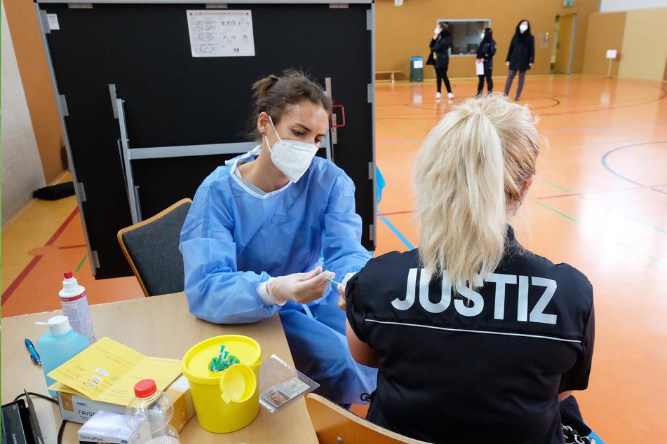 Eine Justizbeamtin wird in der Turnhalle der Justizvollzugsanstalt Volkstedt geimpft.