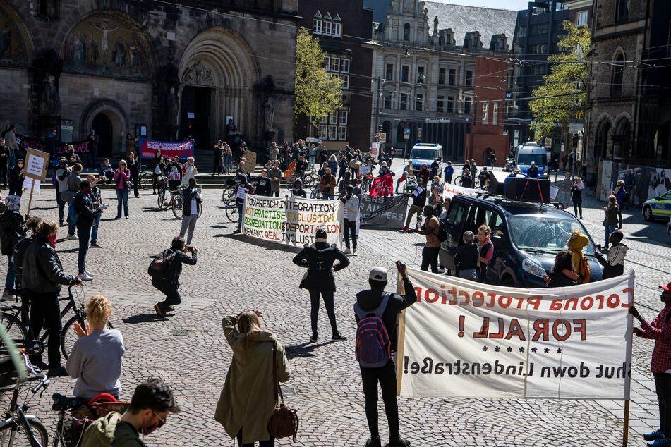 Demonstranten stehen mit Plakaten auf dem Marktplatz. Bei einer Demonstration wird die Schließung der zentralen Erstaufnahmestelle (Zast) an der Lindenstraße gefordert.