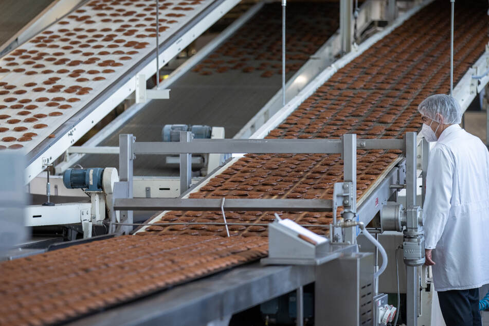 Frisch gebackene Lebkuchen laufen auf einem Band aus einem Ofen in der Produktion des Lebkuchenherstellers Schmidt in Nürnberg.