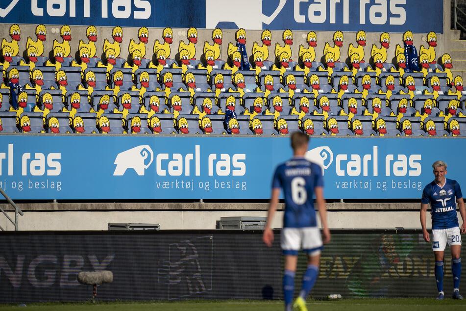 Zwei Spieler des Lyngby BK stehen während ihres Spiels gegen den FC Kopenhagen vor leeren Zuschauertribünen, die durch Abbilder von Enten besetzt wurden. Die Fußballspiele der dänischen Superliga wurden wieder aufgenommen, aber die Zuschauer dürfen die Stadien nicht betreten.