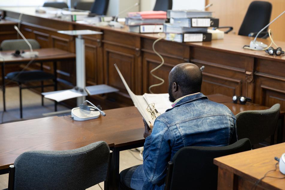 Kurz vor seinem Prozessbeginn hält sich der angeklagte Pastor einen Aktenordner vor sein Gesicht.