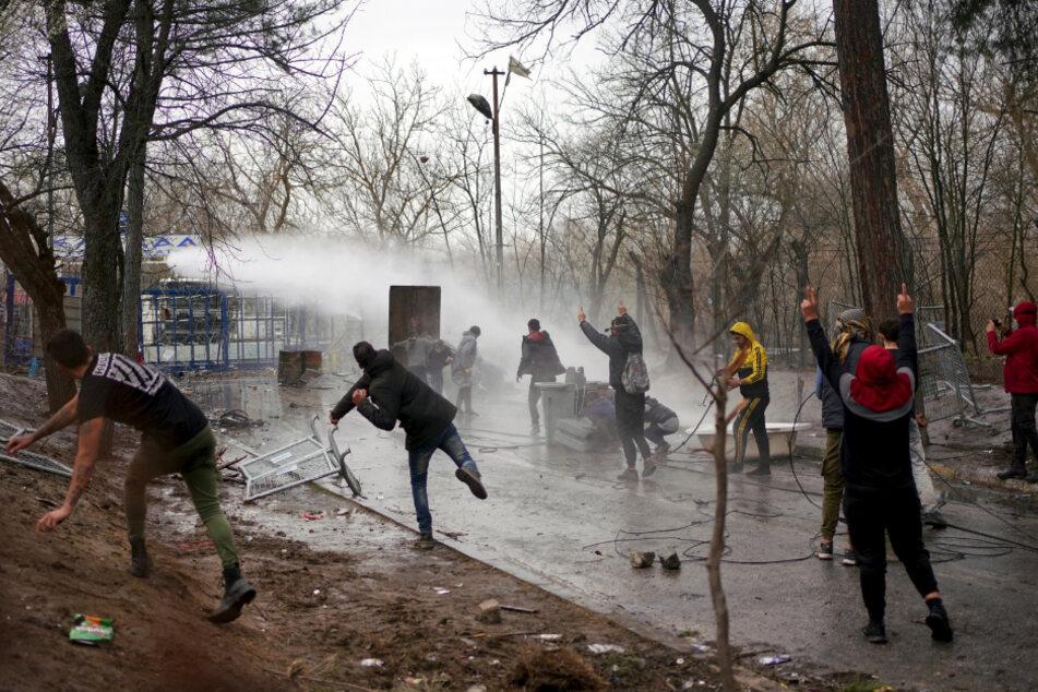 Migranten am Grenzübergang Pazarkule gehen bei Zusammenstößen mit der griechischen Polizei in Deckung, die einen Wasserwerfer zum Einsatz bringt.