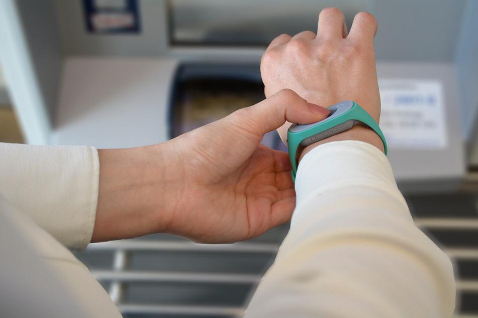 Hygiene-Infrastruktur direkt am Arm: Auf Fingerdruck gibt das Armband-Reservoir Desinfektionsflüssigkeit frei - dosiert genau für eine Handdesinfektion.