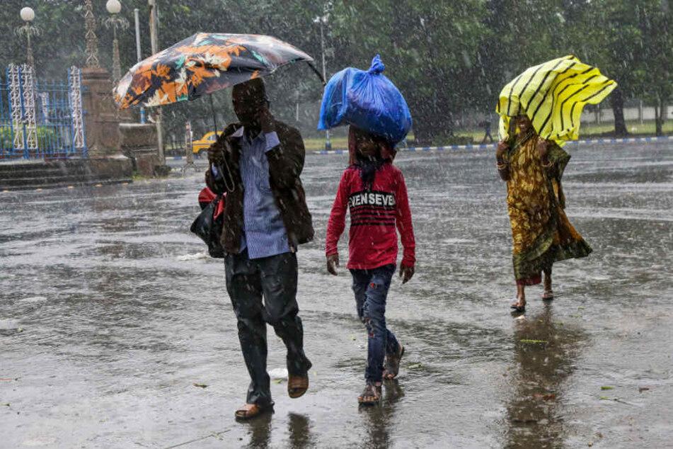 Indien, Kalkutta: Menschen gehen im Regen über die Straße und schützen sich mit Regenschirmen oder anderen Objekten vor dem Wasser.