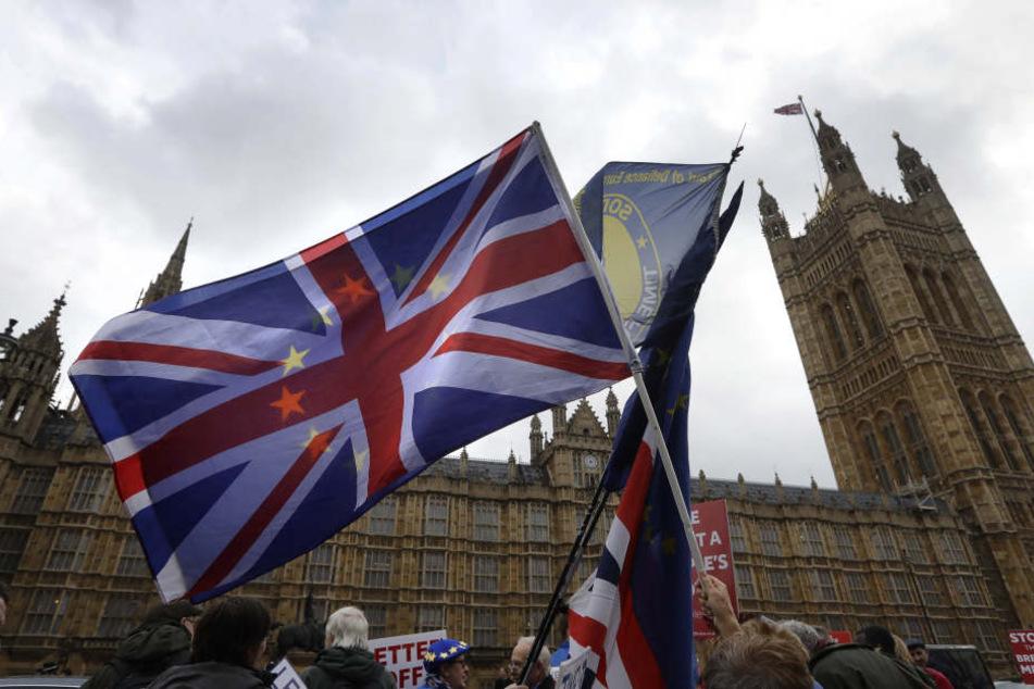 Demonstranten schwenken vor dem Parlament eine britische Fahne.