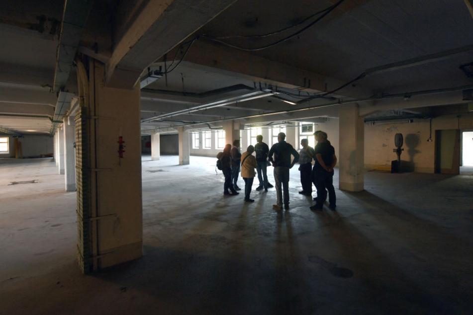 Besucher des ehemaligen KZ Sachsenburg in Frankenberg in einem Raum einer alten Fabrik, der einst als Schlafraum für die hier Inhaftierten genutzt wurde.