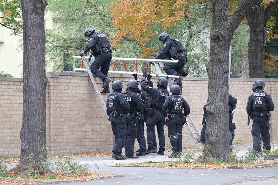 Polizisten mit Schutzhelmen übersteigen eine Mauer am jüdischen Friedhof. Bei Schüssen sind zwei Menschen getötet worden.