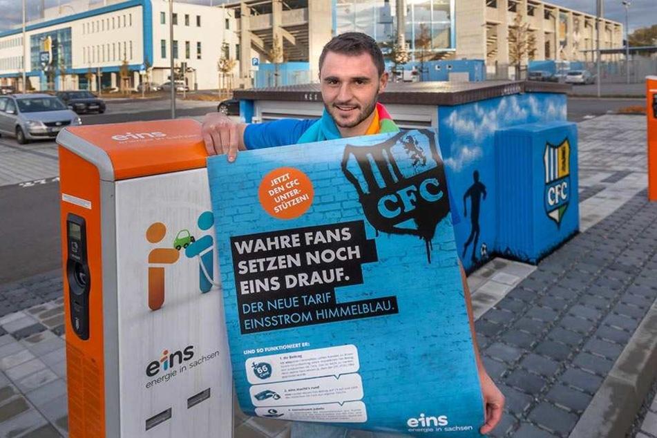 """""""Saft"""" in Himmelblau: CFC-Kapitän Kevin Conrad (26) an  einer neuen E-Ladesäule vor dem Stadion. Er zeigt ein Plakat zum neuen CFC-Fantarif."""