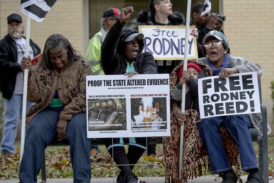 Frauen sitzen auf einer Bank und halten Protestplakate gegen die Hinrichtung von Rodney Reed während einer Demonstration in der Nähe des Büros vom Staatsanwalt des Landkreis Bastrop.